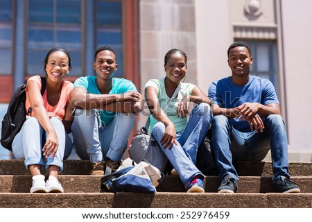 group of happy african student sitting outside college building - stock photo