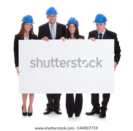 Group Of Happy Architects Holding Blank Placard Over White Background
