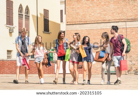 Group of happy best friends with shopping bags in the city center - Tourists walking and having fun in the summer around the old town - University students during a break in a sunny day - stock photo