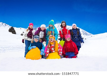 Group of happy boys and girls some with sled, standing together in snow