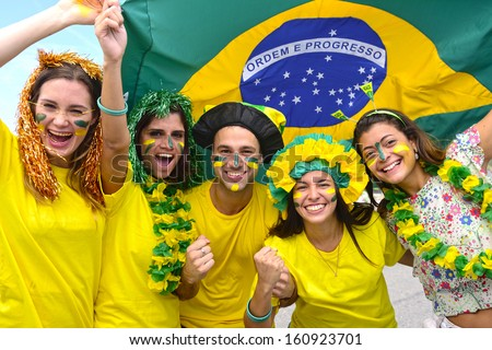 Group of happy brazilian soccer fans commemorating victory,with the flag of Brazil swinging in the air. - stock photo