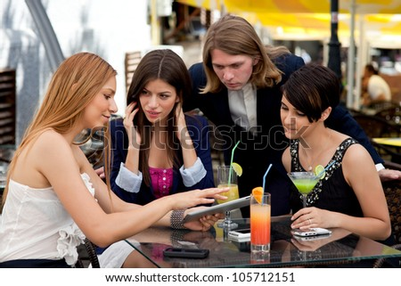 Group of happy business partners or friends enjoy colorful cocktails and talk outdoors. They use tablet and smart phones. - stock photo