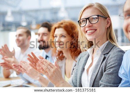 Group of happy business people applauding at conference with smiling blonde in front - stock photo