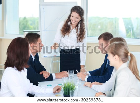 Group of happy business people discussing papers at meeting