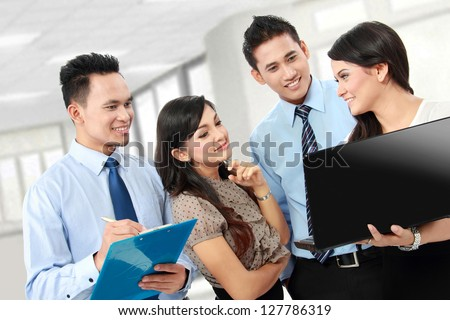 group of happy business people doing presentation with laptop during meeting - stock photo
