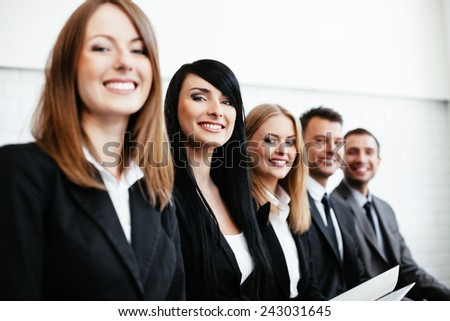 Group of happy business people sitting in a row - stock photo