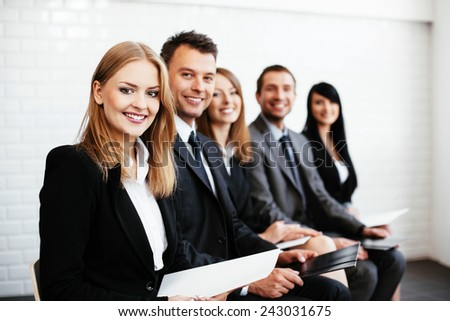Group of happy business people sitting in a row