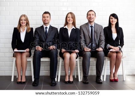 Group of happy business people sitting on chairs