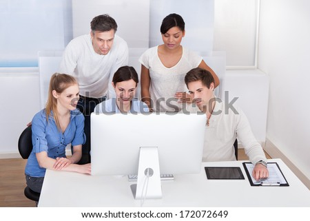 Group Of Happy Businesspeople Working On Computer At Office - stock photo