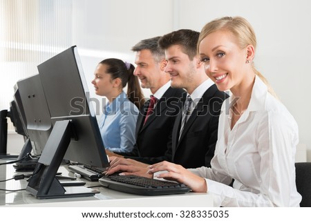 Group Of Happy Businesspeople Working On Computers At Desk