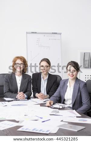 Group of happy businesswomen sitting beside large desk at light office - stock photo