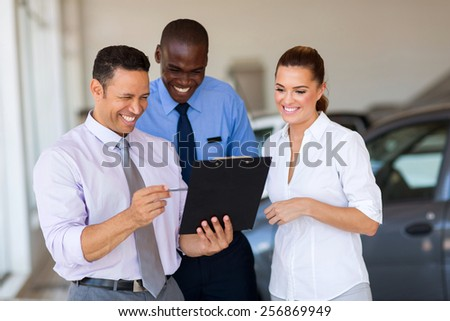 group of happy car sales consultants working inside vehicle showroom - stock photo