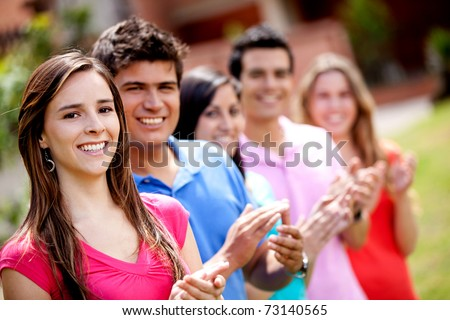 Group of happy casual friends applauding outdoors