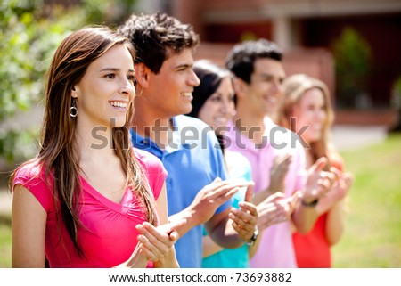 Group of happy casual friends applauding outdoors - stock photo