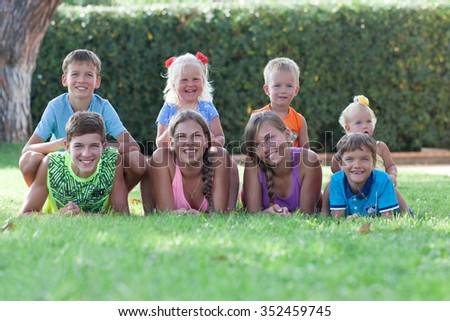 Group of happy cheerful beautiful children lying on grass in park, outdoor, Italy - stock photo
