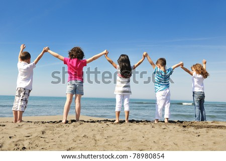 group of happy child on beach who have fun and play games - stock photo