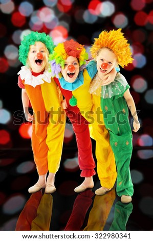 Group of happy children dressed up as colorful funny clowns - stock photo
