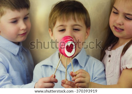 Group of happy children eating lollipops
