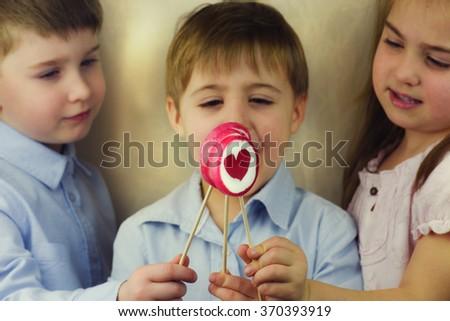 Group of happy children eating lollipops - stock photo