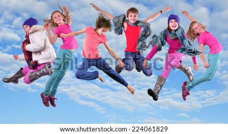 Group of happy children exercising, jumping and having fun in the bright blue cloudy sky Childhood, happiness, active lifestyle concept - stock photo