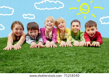 Group of happy children lying on a grass and stretching their hands - stock photo
