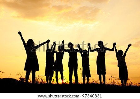 Group of happy children playing at summer sunset in nature - stock photo
