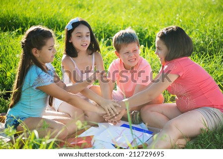 Group of happy children playing on green grass - stock photo