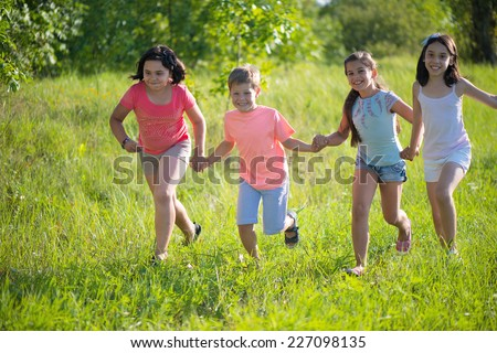 Group of happy children playing on meadow - stock photo