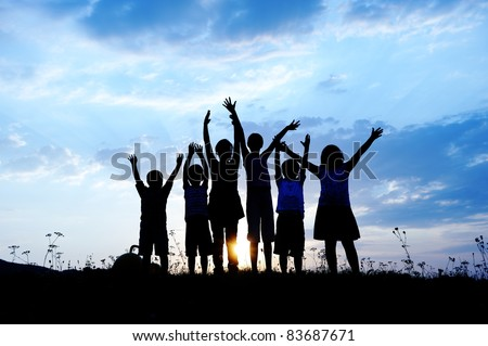 group of happy children playing on meadow, blue sky, summertime - stock photo