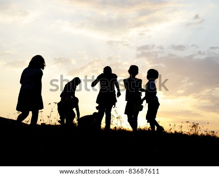 Group of happy children playing on meadow, sunset, summertime