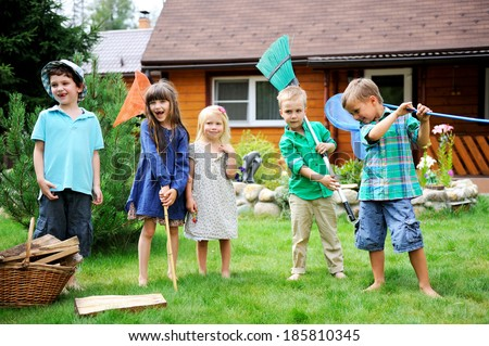 Group of happy children playing outdoors in front of country house