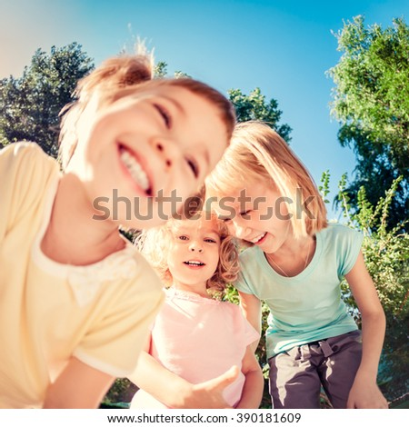 Group of happy children playing outdoors in spring park. Low angle view portrait - stock photo