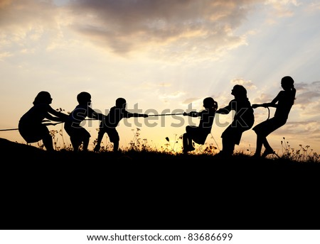 Group of happy children playing tug war on meadow, sunset, summertime