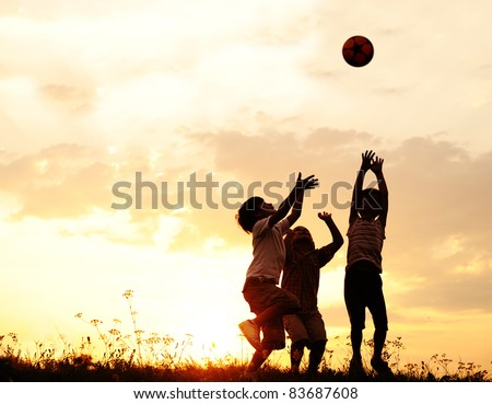 Group of happy children playing with ball on meadow, sunset, summertime - stock photo