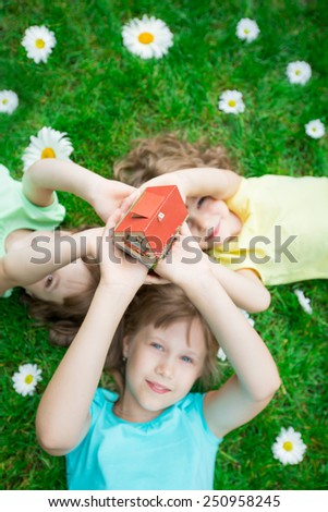 Group of happy children showing model house outdoors in spring park. Real estate concept. Family moving and renovation. - stock photo
