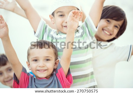 Group of happy children with hands up - stock photo
