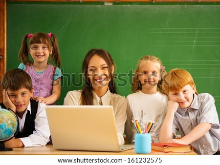 Group of happy classmates with their teacher in class near blackboard  - stock photo