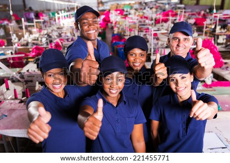 group of happy clothing factory co-workers thumbs up - stock photo