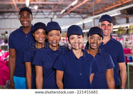 group of happy clothing factory workers inside production area - stock photo