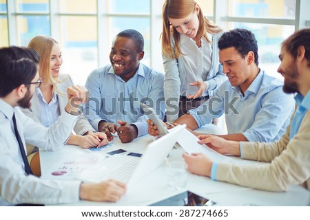 Group of happy colleagues communicating in office - stock photo