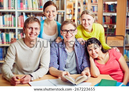 Group of happy college friends sitting in library - stock photo