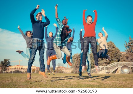Group of Happy College Students Jumping at Park - stock photo