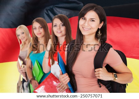 Group Of Happy College Students Standing In Front Of German Flag - stock photo