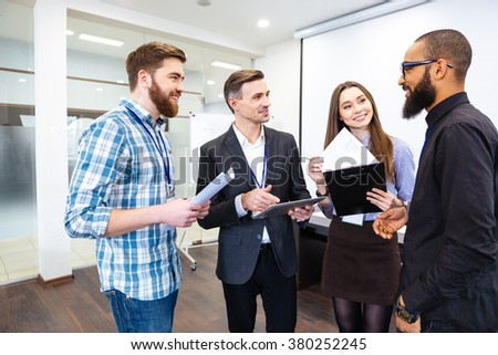 Group of happy confident young business people on meeting with team leader - stock photo