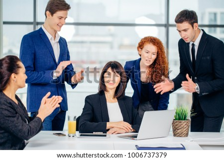 Group of happy diverse male and female business people in formal gathered around laptop computer in office
