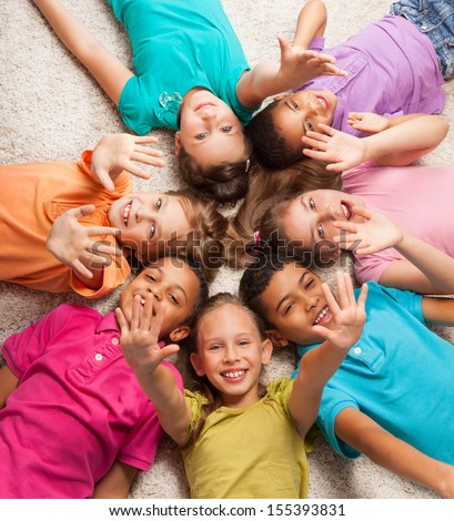 Group of happy diversity looking kids laying in star shape on the floor with lifted kids - stock photo