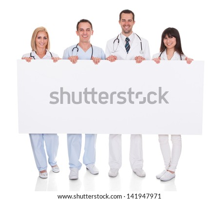 Group Of Happy Doctors Holding Placard Over White Background - stock photo
