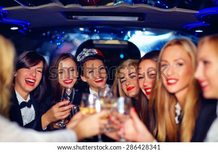 group of happy elegant women clinking glasses in limousine, hen party - stock photo