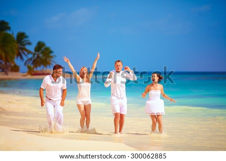 group of happy excited friends having fun on tropical beach, summer vacation - stock photo