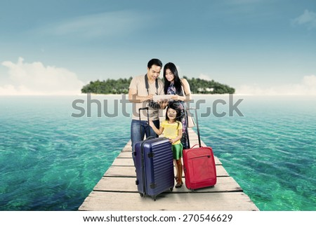 Group of happy family traveling together and look at a digital map on the tablet - stock photo